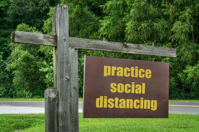 practice social distancing - park or trailhead sign against gree